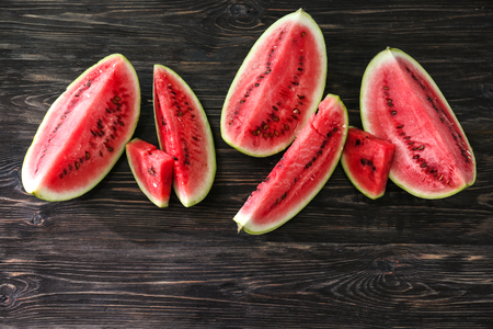Pieces of ripe watermelon on wooden background