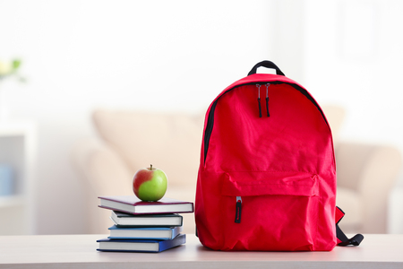 School backpack with notebooks and apple on table