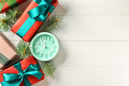 Alarm clock with gifts on light background. Christmas countdown