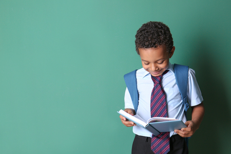 Cute African-American schoolboy reading book on color background Stock Photo