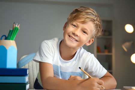 Cute little boy doing his lessons at home Standard-Bild