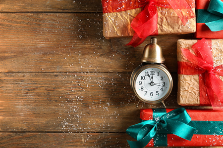 Composition with alarm clock and gifts on wooden background. Christmas countdown