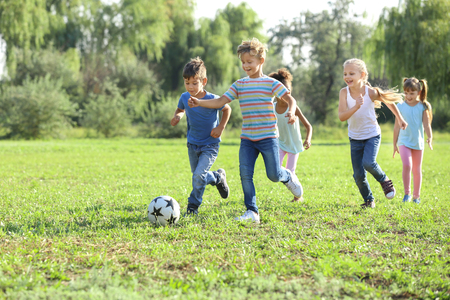 Cute little children playing football outdoors Archivio Fotografico