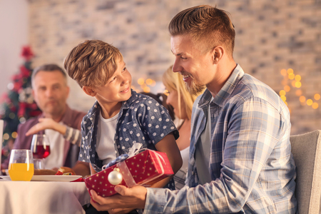 Cute boy and his father with Christmas gift at home Stock Photo