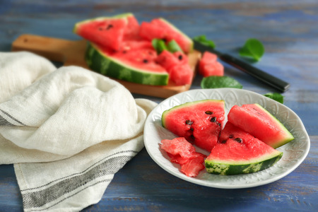 Plate with fresh slices of watermelon on wooden background Foto de archivo