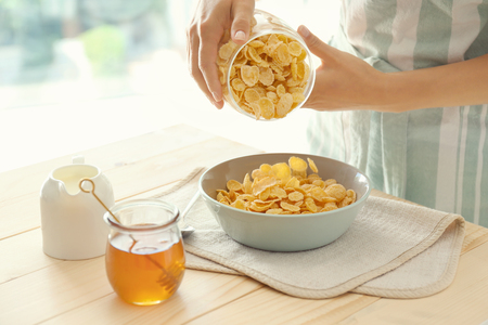 Woman pouring corn flakes into bowl from jar at table 免版税图像