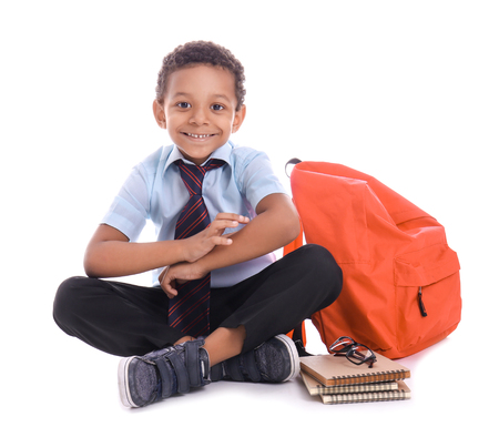 Cute African-American schoolboy with backpack on white background