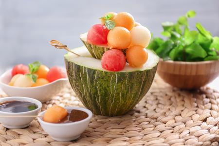 Tasty melon dessert with balls on wicker mat Stockfoto - 114746415