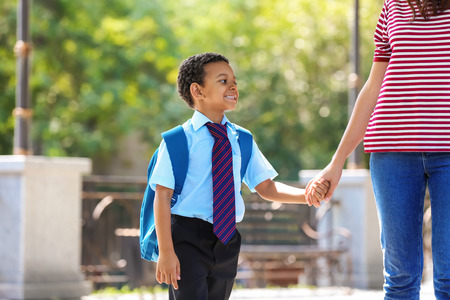 Cute African-American schoolboy going to school with mother Imagens