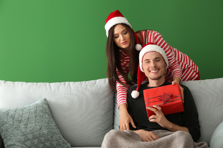 Portrait of cute young couple with Christmas gift  on color background 版權商用圖片