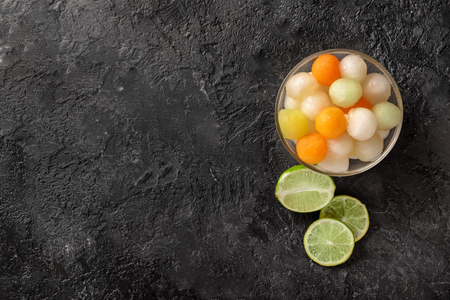 Bowl with delicious melon balls and lime on grunge table