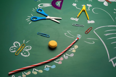 Creative composition with school stationery on chalkboard
