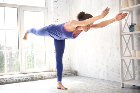 Sporty woman practicing yoga indoors Stock Photo