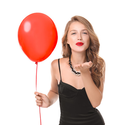 Beautiful young woman with balloon blowing kiss on white background Standard-Bild