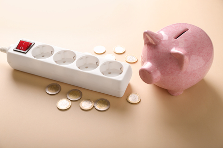 Piggy bank with coins and extension cord on color background. Electricity saving concept