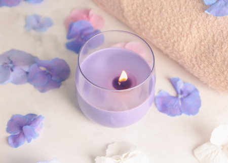 Burning candle with hydrangea flowers on light table