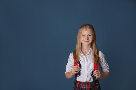 Cute schoolgirl with backpack on color background