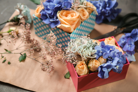 Gift boxes with beautiful flowers on table