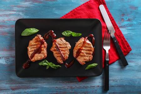 Plate with delicious grilled steaks and sauce on wooden table Stock Photo