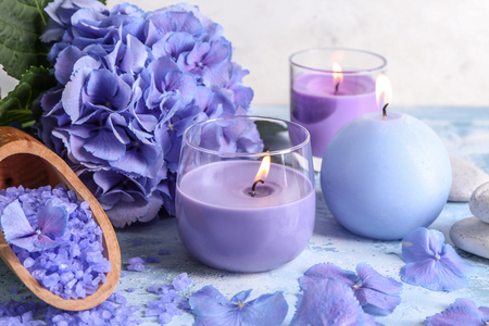 Spa composition with hydrangea flowers and burning candles on color table
