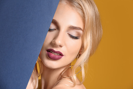 Beautiful young woman with dark lipstick and poster on color background Stock Photo