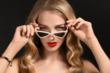 Beautiful young woman with bright red lipstick and sunglasses on dark background Stock Photo