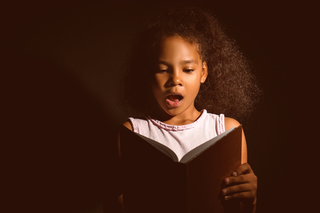 Surprised African-American girl reading book on dark background Stock fotó