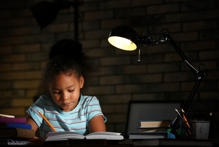 Little African-American girl doing homework in evening at home Stok Fotoğraf