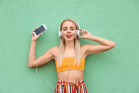 Beautiful young woman listening to music near color wall