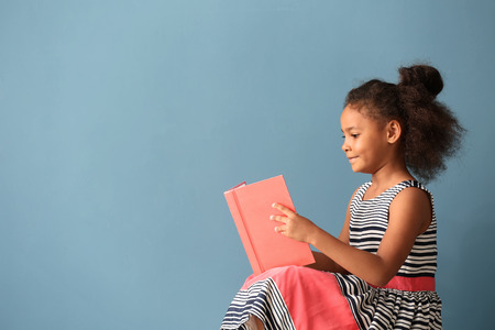 Little African-American girl reading book on color background