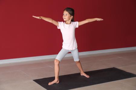 Little girl practicing yoga indoors