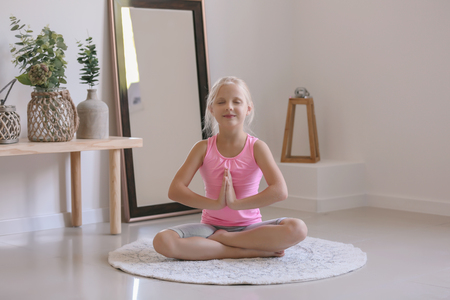 Little girl practicing yoga at home