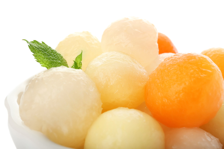 Bowl with delicious melon balls on white background, closeup