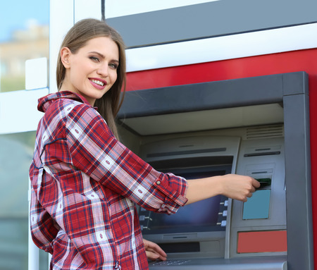 Woman inserting credit card into cash machine outdoors