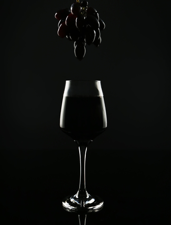 Glass with red wine and tasty fresh grapes on black background 写真素材