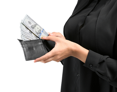 Young woman holding wallet with dollar banknotes on light background, closeup