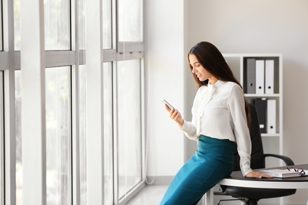 Young businesswoman with mobile phone in office Standard-Bild