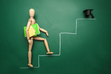 Small wooden mannequin going upstairs to mortarboard on color background