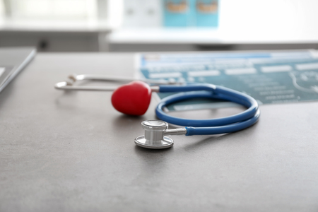 Medical stethoscope and red heart on grey table. Cardiology concept