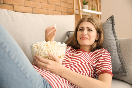 Emotional young woman eating popcorn while watching TV at home