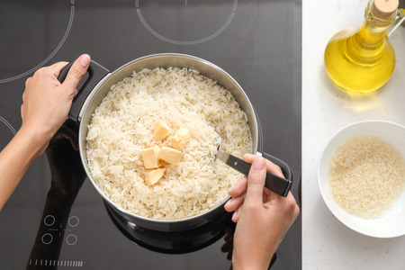 Woman cooking rice on stove in kitchen