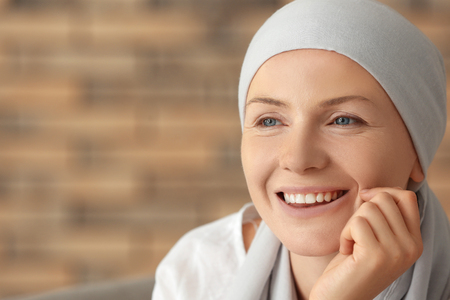 Portrait of happy woman after chemotherapy on blurred background Standard-Bild