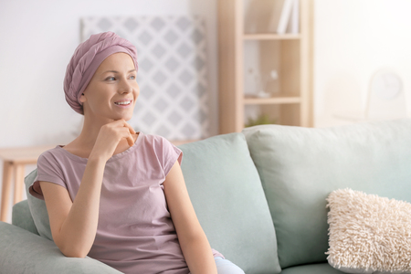 Happy woman after chemotherapy  sitting on sofa at home Archivio Fotografico