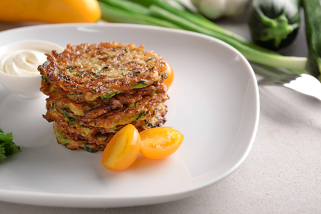 Tasty zucchini pancakes with tomatoes on plate