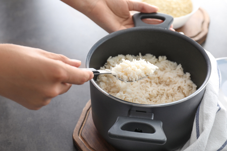 Woman with saucepan full of tasty rice Stock Photo