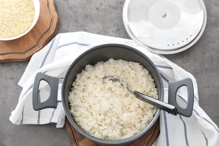Saucepan with boiled rice on grey table Reklamní fotografie