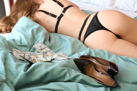 Young prostitute in lingerie and with money lying on bed
