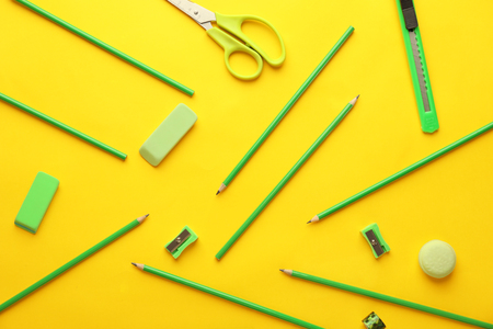 Composition with different school stationery on color background
