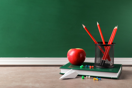 School stationery with apple on table against chalkboard