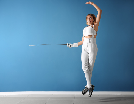 Young female fencer against color wall